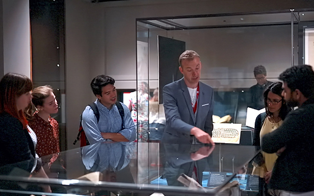 Five people around a glass case listening to a man speaking