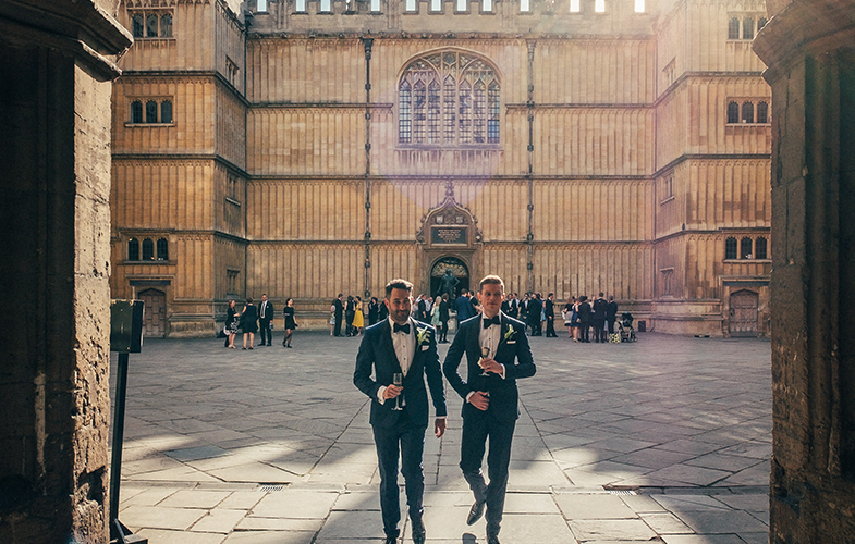 Two grooms at a wedding reception in Old School's Quadrangle