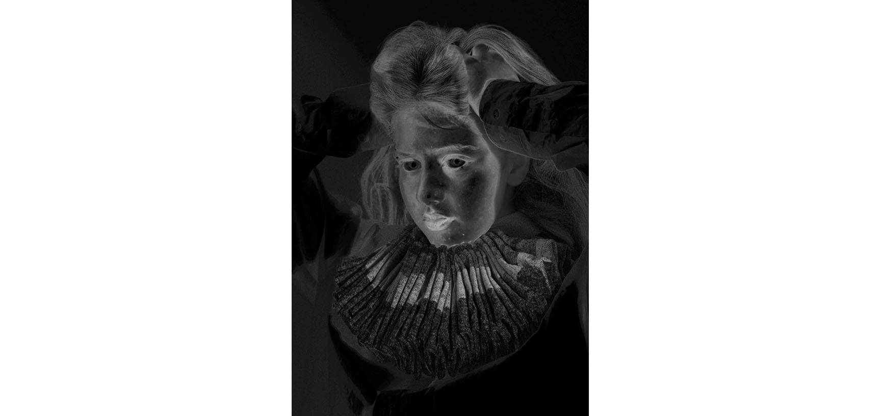 A negative image of a woman's face - she puts her hands through her hair and looks to the side of the camera