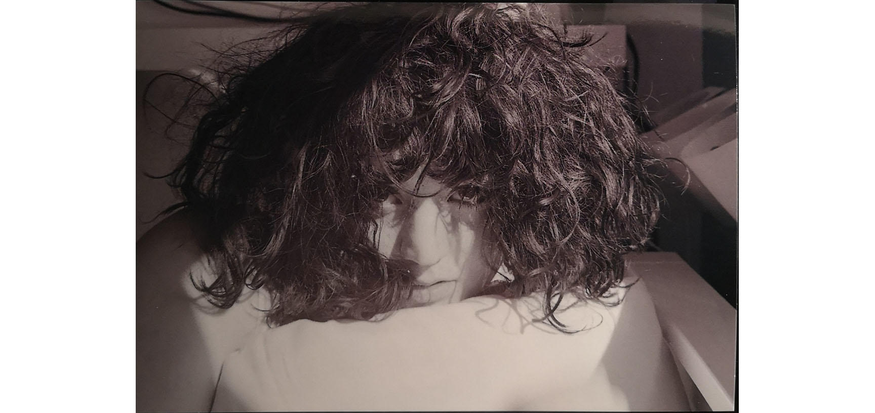 A close up on a woman's face - she looks directly at the camera and her hair tumbles down over her face