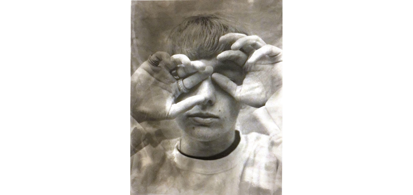A sepia image of a person. Their head faces the camera but their eyes are covered by their hands - one hand covering an eye, the other makes a circle around the other eye