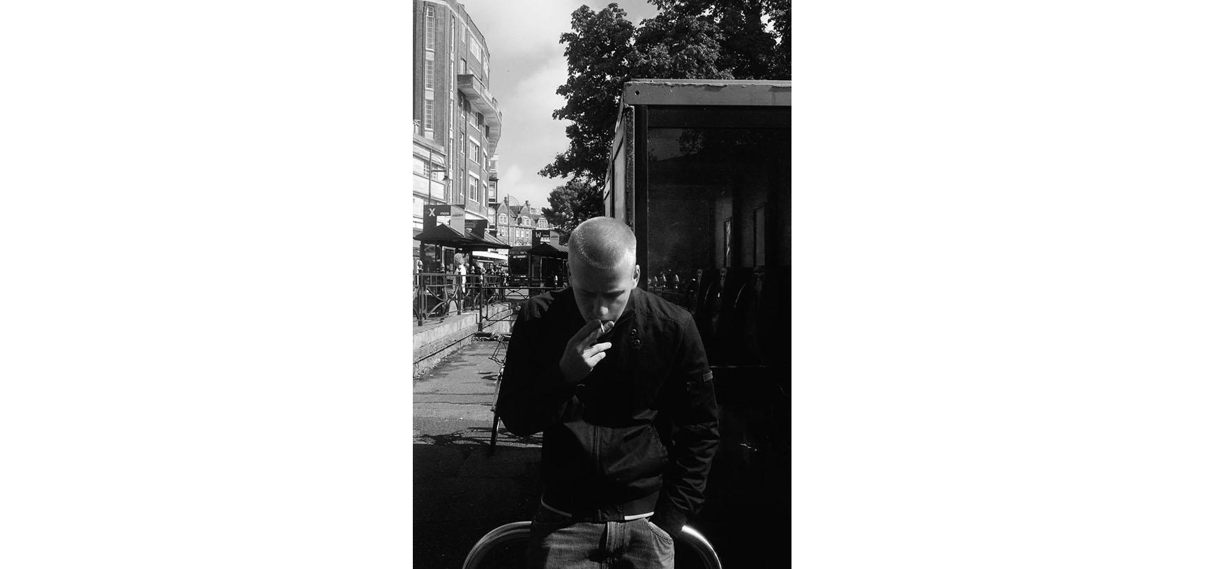 A black and white photograph of a man standing, head down, smoking a cigarette