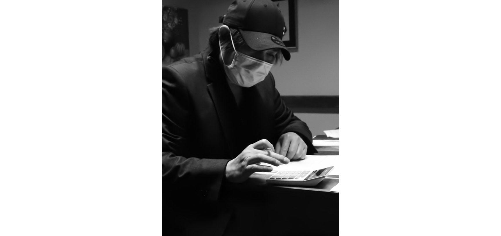 A black and white photograph of a man sitting at a table. He is about to write in a notebook. He wears a baseball cap on his head and a face mask across his mouth.