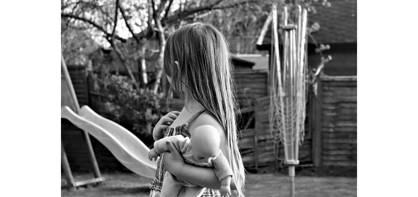 A black and white photograph of a young child. They are looking away from the camera towards a slide in the background. They hold a doll in their left hand.