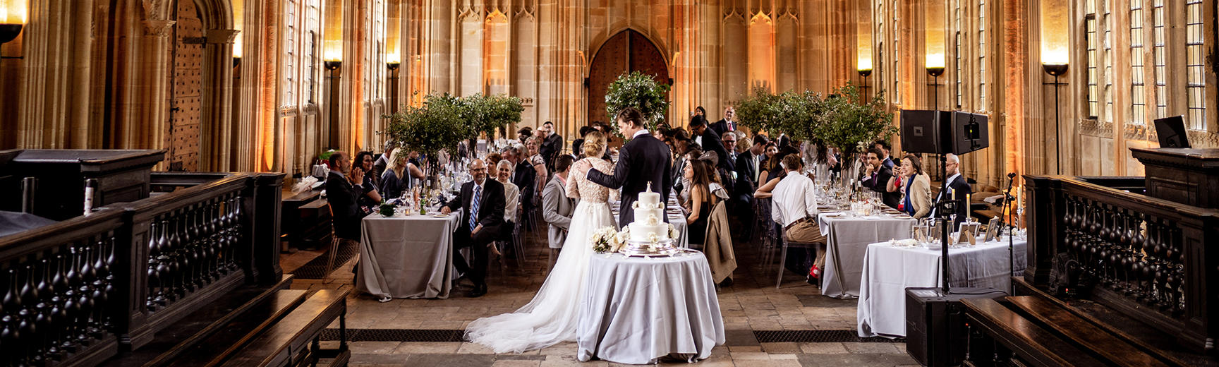 Newlyweds standing in front of dinner tables of wedding guests in Divinity School