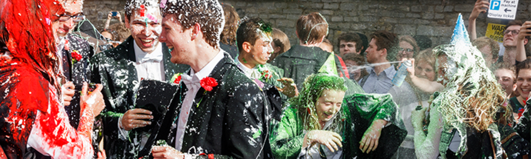 Oxford students celebrating finishing exams by spraying foam and champagne