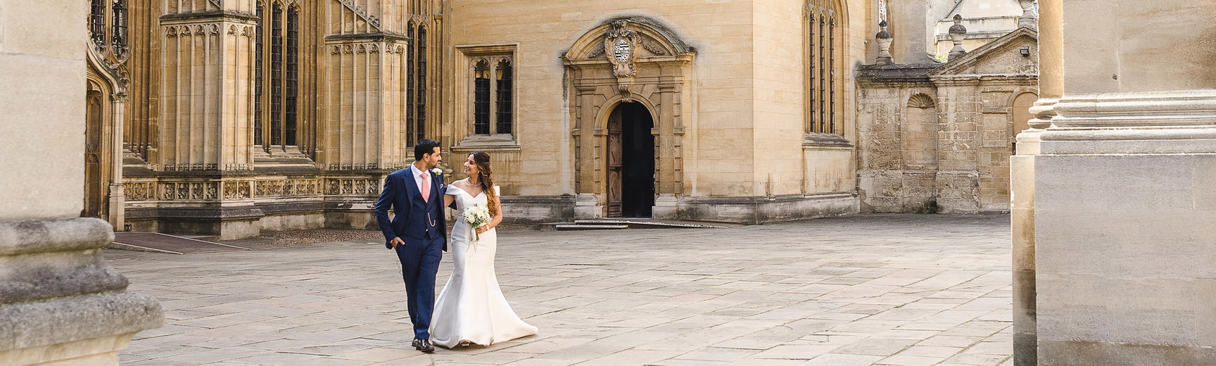 A bride and groom smiling outside the Divinity School