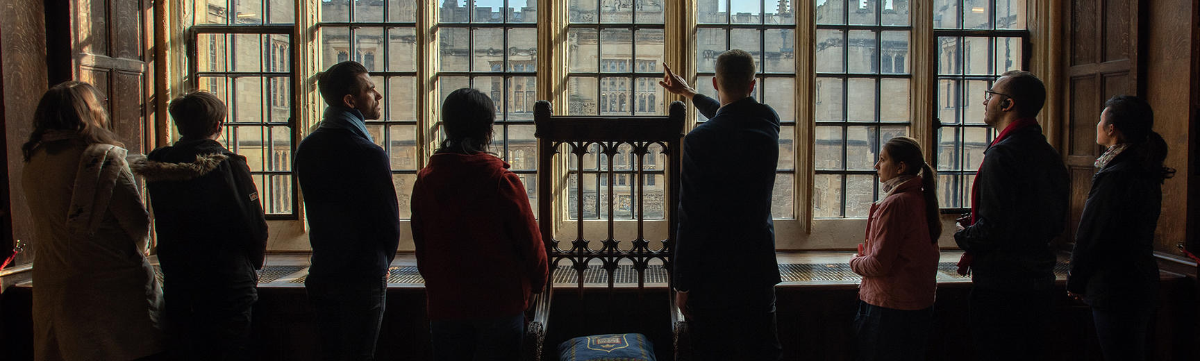 Tour guide showing visitors the view from the Old Bodleian Library