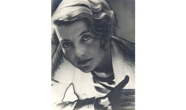 A photograph of a young woman looking directly at the camera