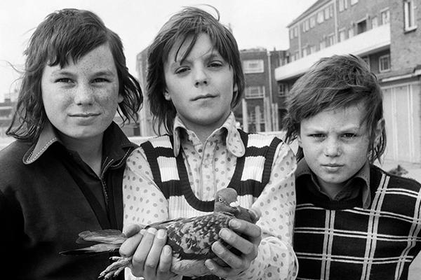 Black-and-white photograph of three children and a pigeon