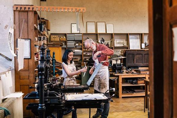 Two people look at a print in front of an old printing press