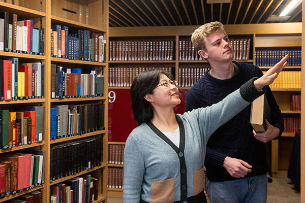 Two people look at a bookshelf in a library
