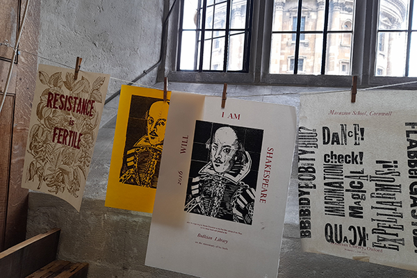 Image of a string hanging across the picture with pieces of paper hanging from it on pegs with examples of letterpress printing on them