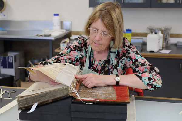 Conservation staff repairing the damaged and broken spine folds of a book, Bodleian Libraries