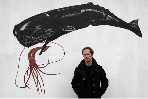A man standing under a wall print of a whale