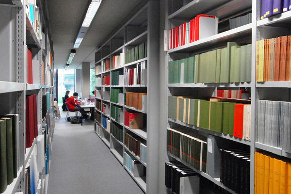 Books on library shelves with desks in the distance
