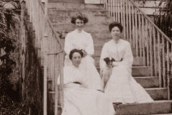 Black-and-white photograph of three women sitting on steps