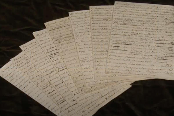 8 pages of a handwritten manuscript laid out in a fan