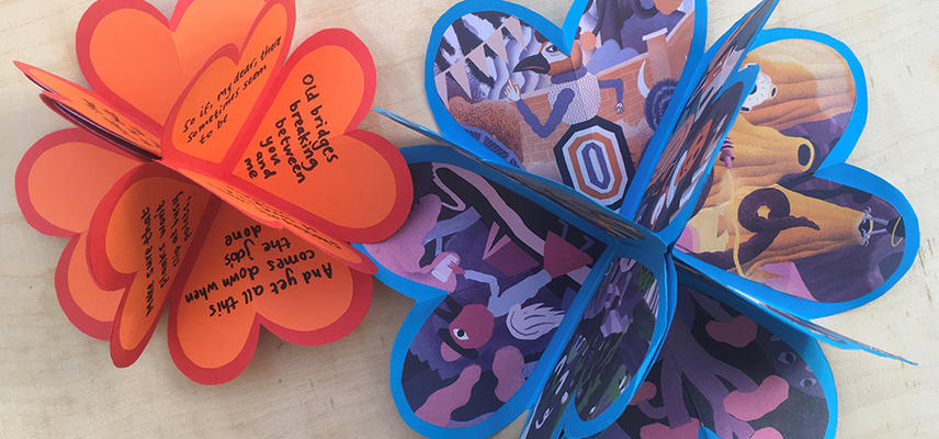 Image of two heart shaped paper craft items with handwritten text on one and images from a cartoon stuck on the other