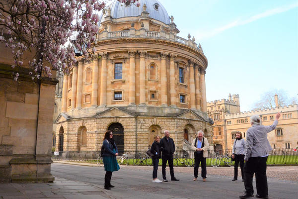A group of five people look towards a tour guide who is point out a historic building detail, in the background is the Radcliffe Camera