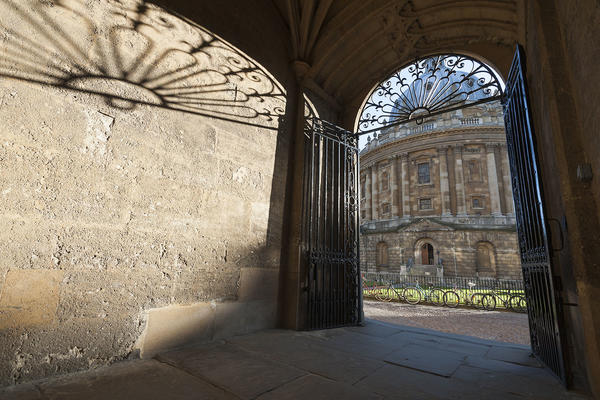 A view through a gateway of the Radcliffe Camera - a large domed building in the centre of a public square