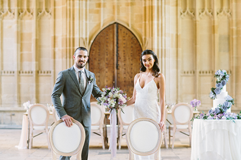 Image of a man and woman in wedding outfits, standing next to each other facing the camera holding a bunch of wedding flowers together