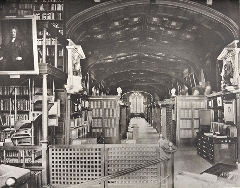 A black and white image of Duke Humfrey's Library taken in 1914 - a large room with wooden ceiling and bookcases stretching the length of the room