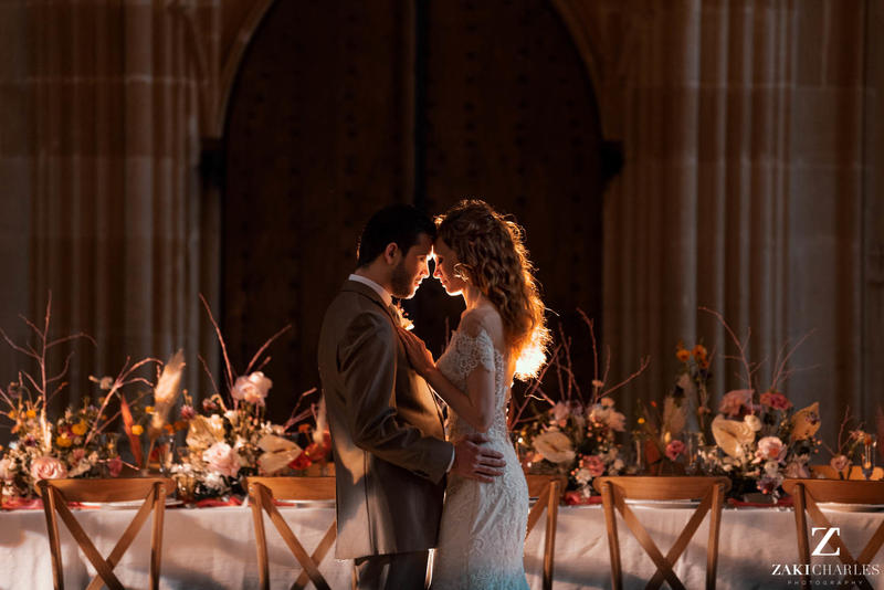 A man and woman look at each other in front of an ornately decorated table