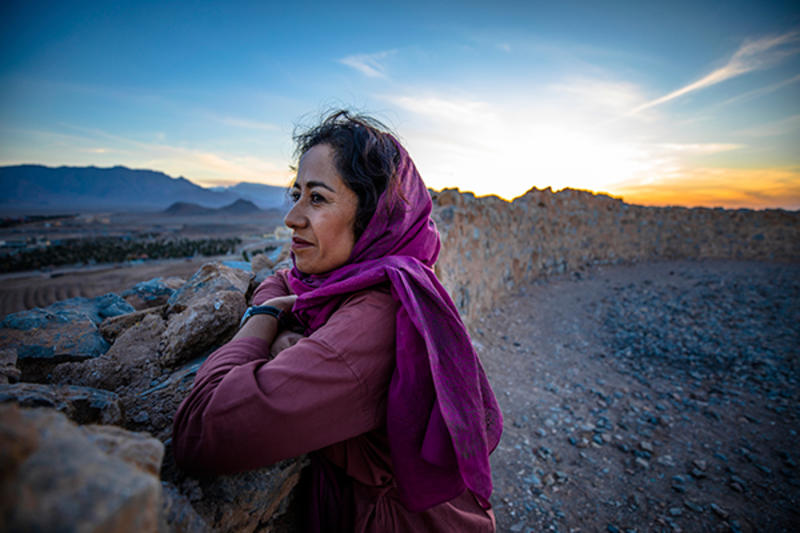 Image of an asian woman in a barren landscape looking into the distance with the sun setting behind her