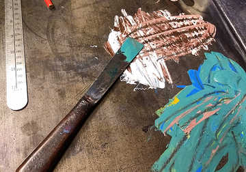 Image looking overhead of a palette knife and some paint spread on a metal table, tools for linocut printing